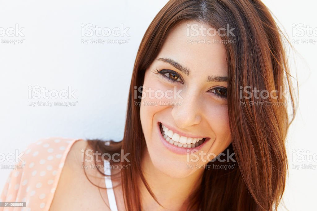 Portrait Of Pretty Young Woman Standing By Wall stock photo