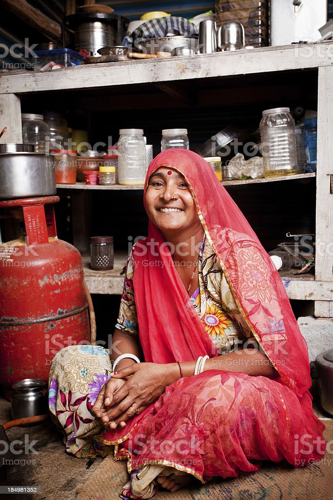 Portrait of Rajasthani Indian female sitting in her Kitchen stock photo