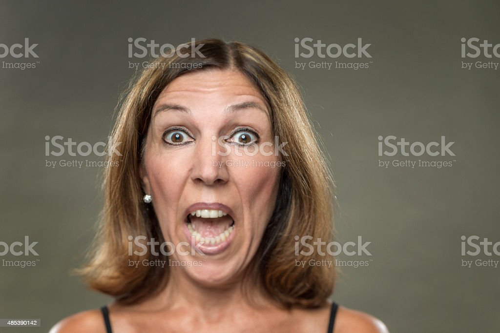 Portrait of real woman, with big eyes, screaming, looking scared stock photo