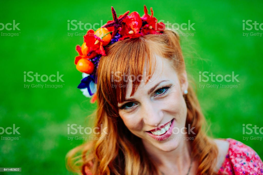 Portrait of red head woman in nature with hair accessory stock photo