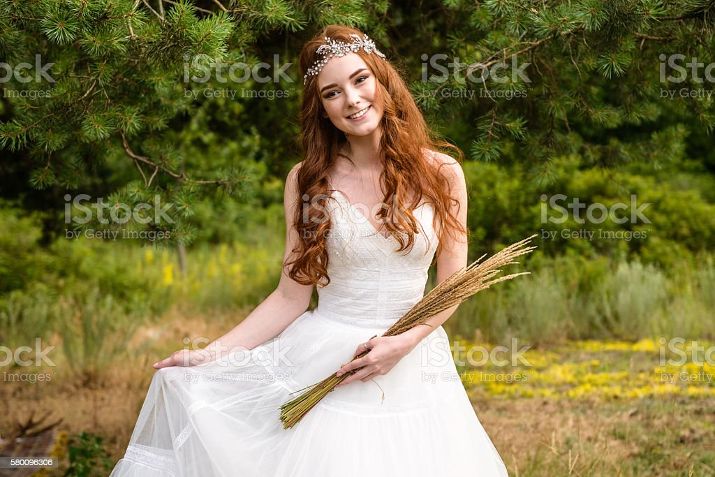 portrait of red-haired bride in the forest stock photo