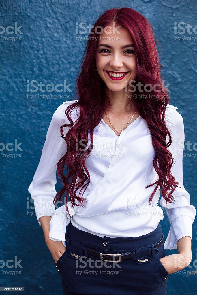 Portrait of redhaired, rehead laughing smiling girl with pink hair stock photo