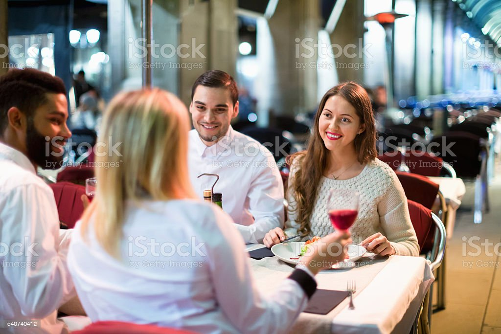 Portrait of relaxed adults having dinner outdoors stock photo