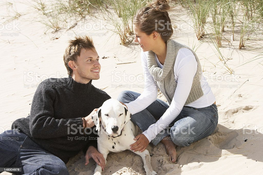 Portrait Of Romantic Teenage Couple On Beach With Dog royalty-free stock photo