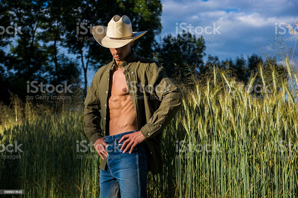 Portrait of rustic man in cowboy hat with unbuttoned shirt stock photo