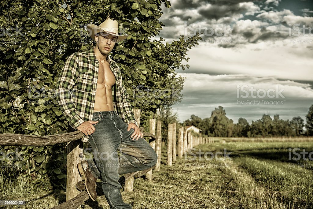 Portrait of rustic man in hat with unbuttoned shirt leaning stock photo