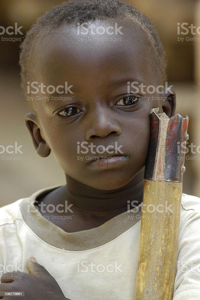 Portrait of Sad African Boy Holding Stick stock photo