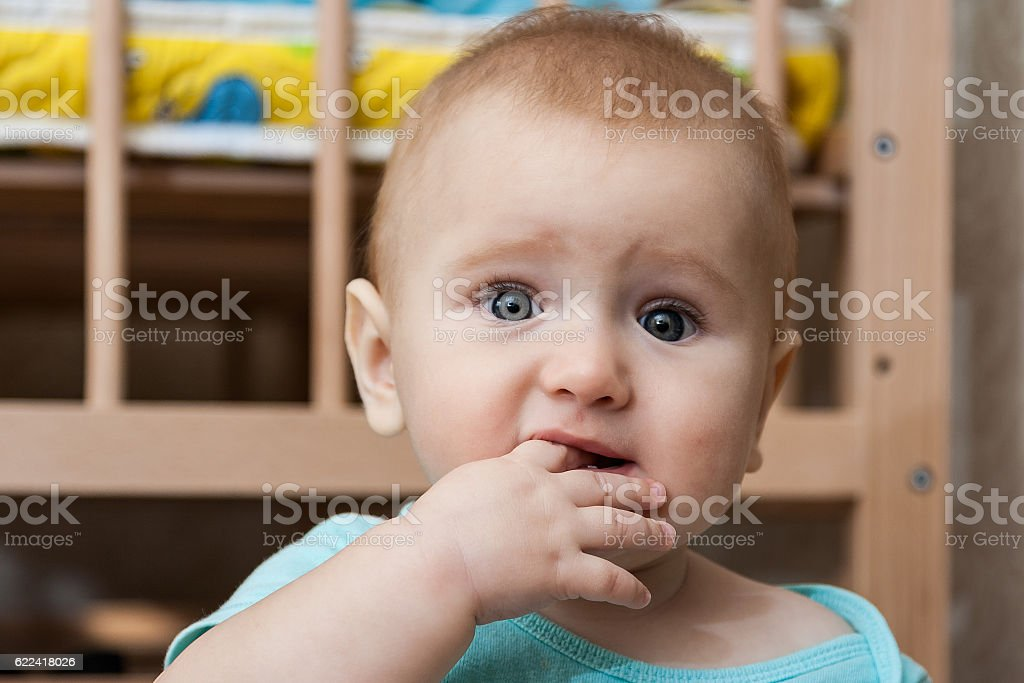 Portrait of sad charming baby with finger in his mouth stock photo