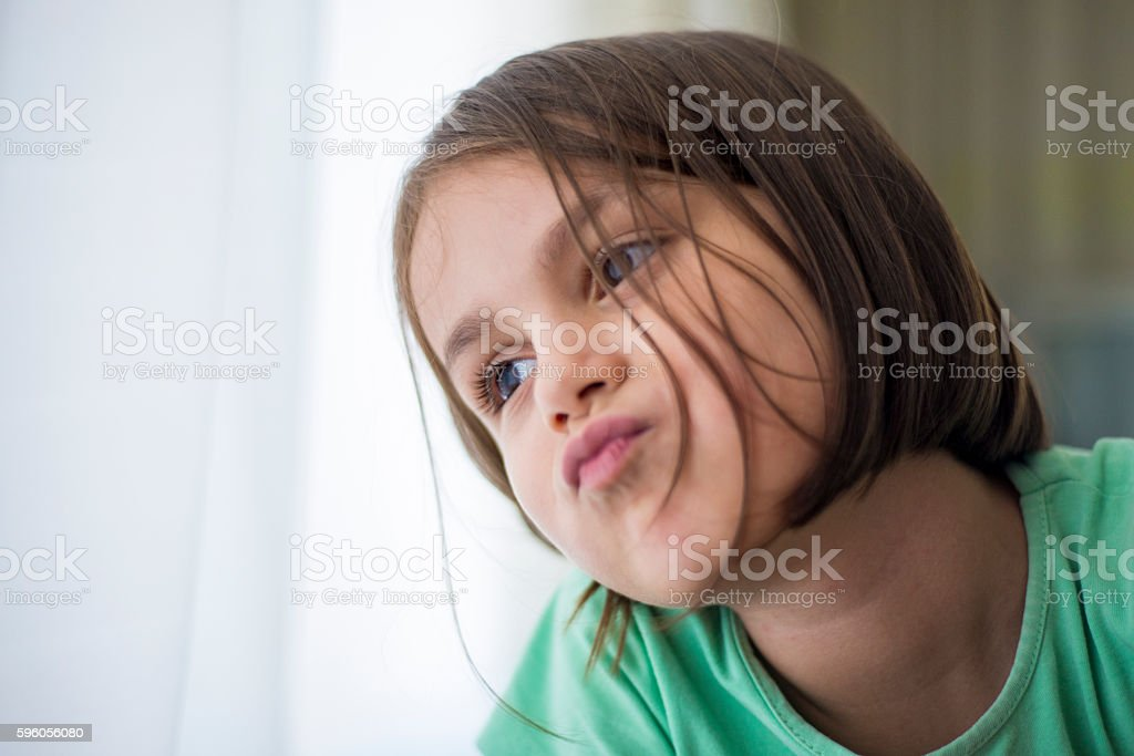 Portrait of sad girl looking away next to window stock photo