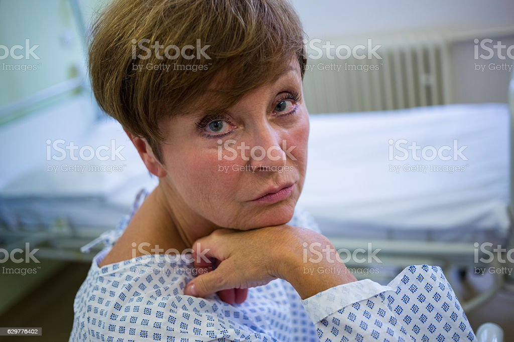 Portrait of sad senior patient sitting on a bed stock photo