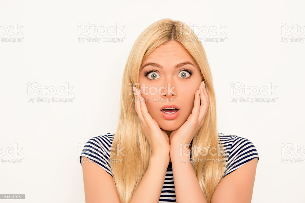 Portrait of sad shocked young woman touching face stock photo