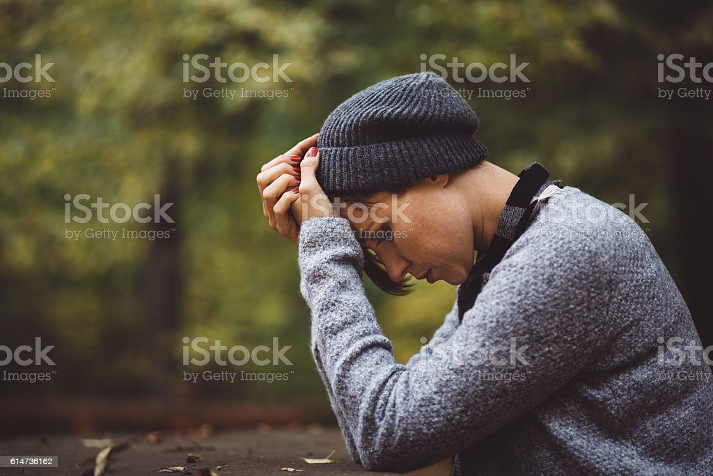 Portrait of sad woman sitting alone in the forest. Solitude stock photo