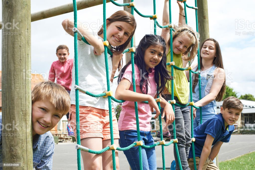 Portrait Of School Pupils Playing On Climbing Frame stock photo