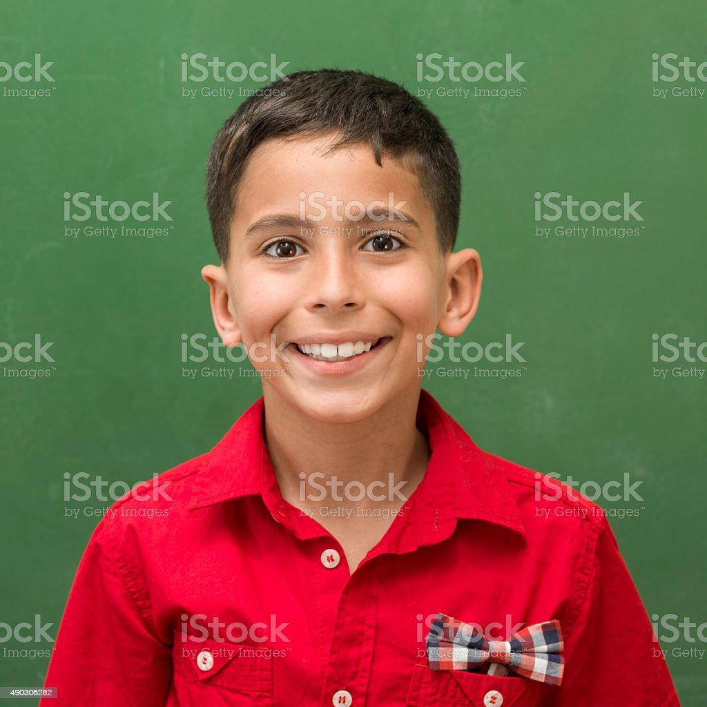 Portrait of schoolboy posing in front of blackboard stock photo