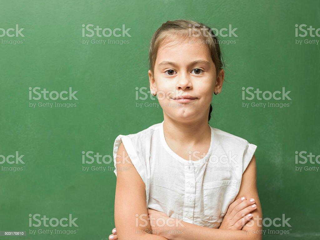 Portrait of schoolgirl posing in front of blackboard stock photo