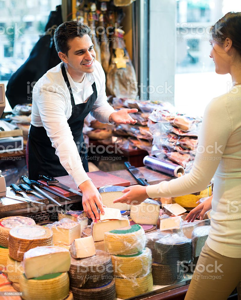 Portrait of seller offering different cheese stock photo