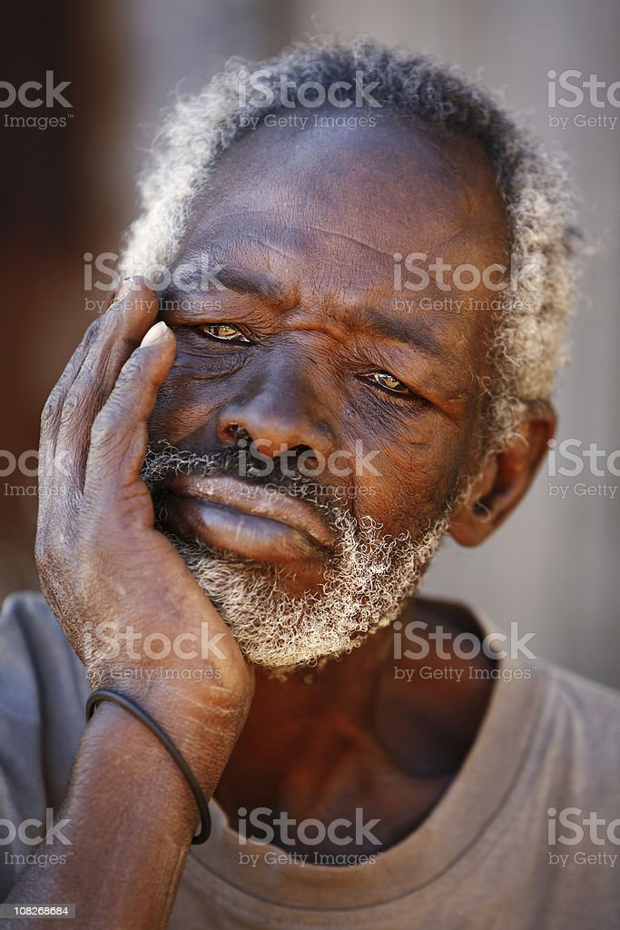 Portrait of Senior African Man Resting Chin in Hand stock photo