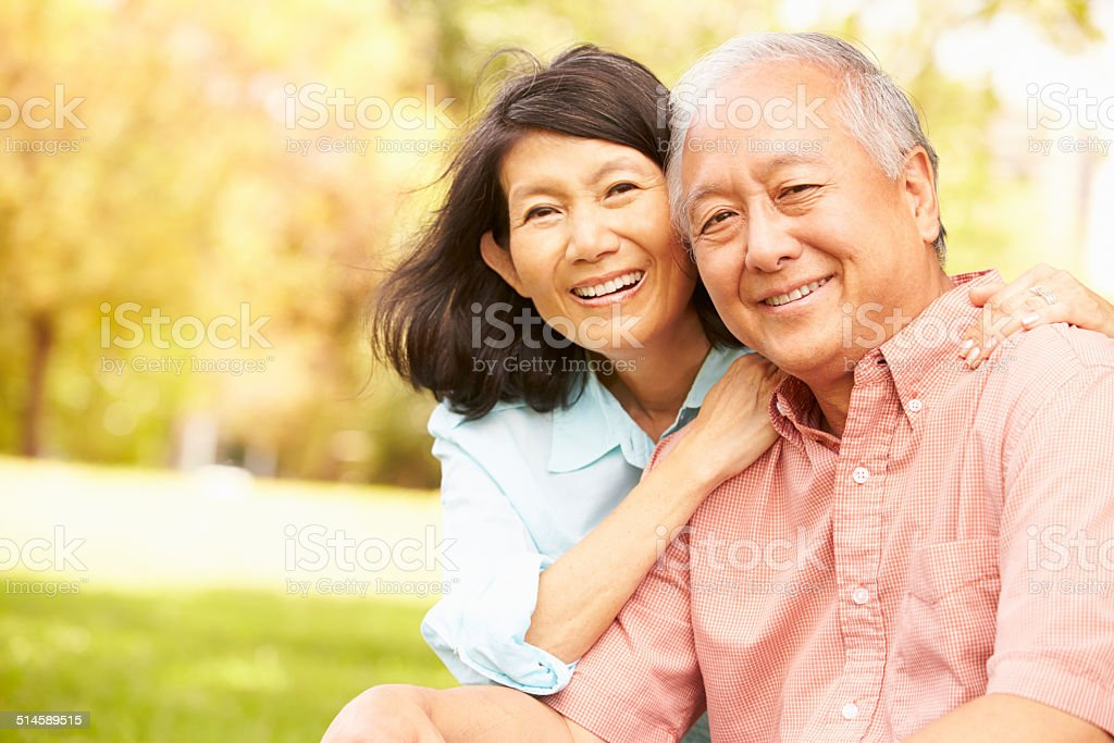 Portrait Of Senior Asian Couple Sitting In Park Together stock photo