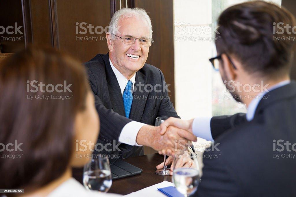 Portrait of Senior Businessman Shaking Hands with Partner stock photo