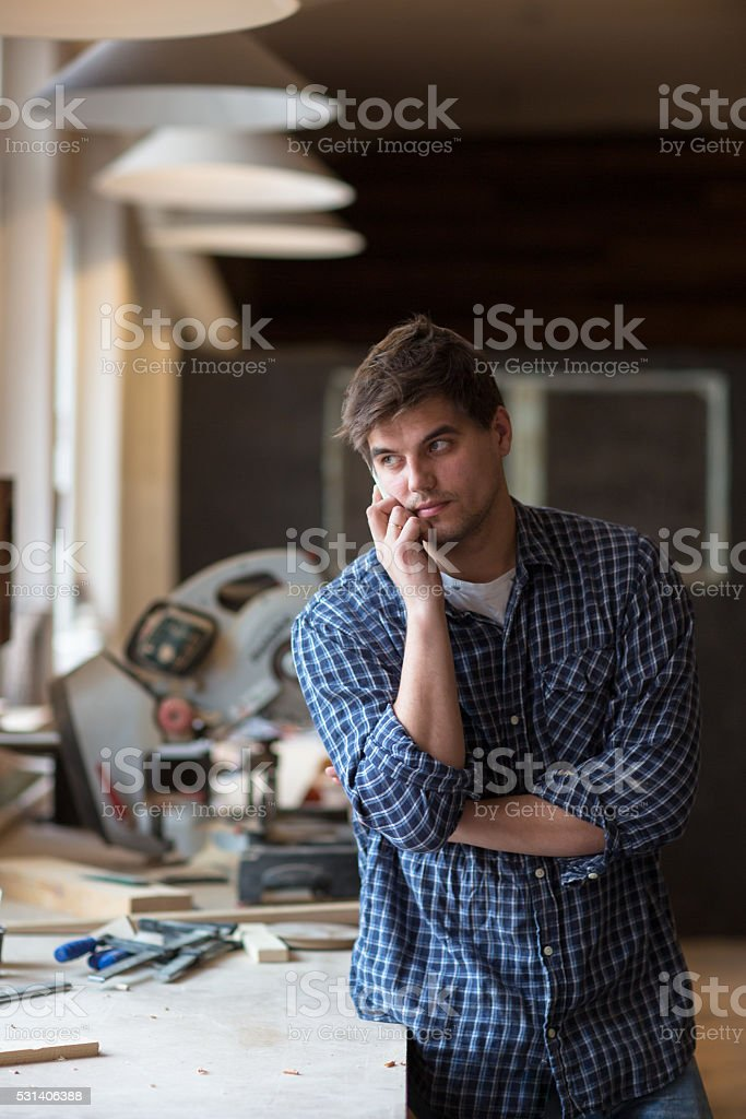 Portrait of senior carpenter working at his workshop while stay stock photo