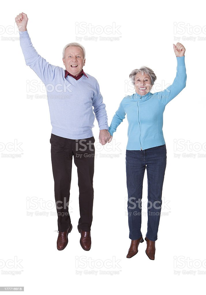 Portrait Of Senior Couple Jumping In Joy royalty-free stock photo