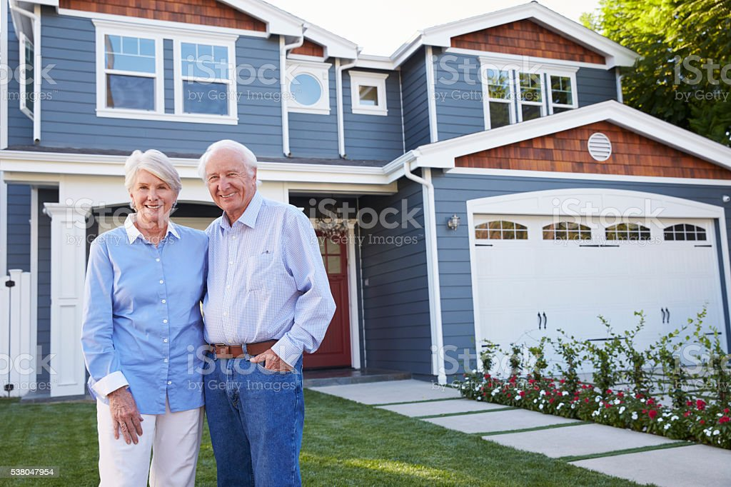 Portrait Of Senior Couple Standing Outside House stock photo