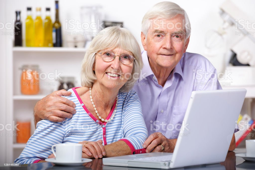 Portrait Of Senior Couple Using Laptop In A Domestic Kitchen stock photo
