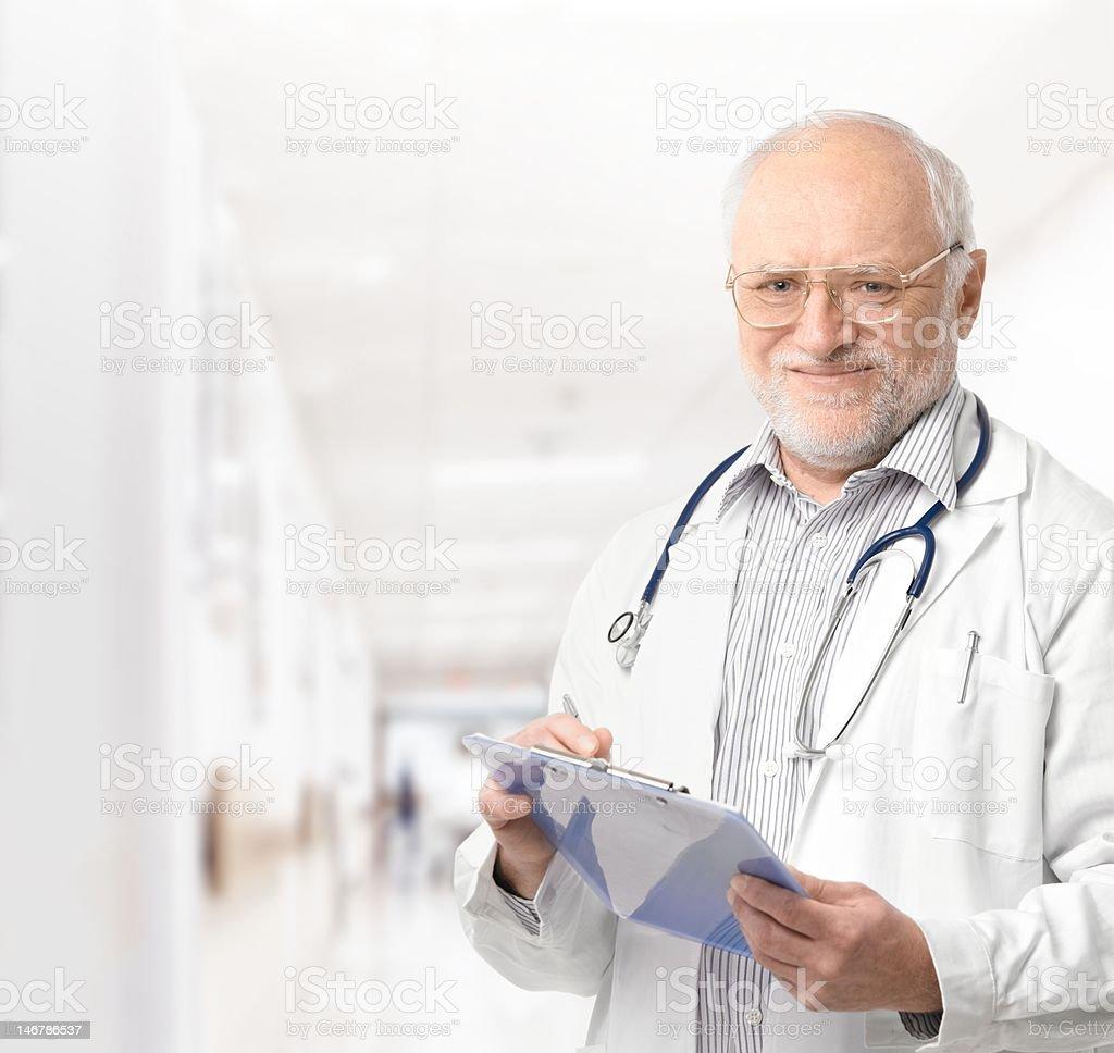 Portrait of senior doctor on hospital corridor royalty-free stock photo