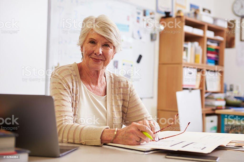 Portrait of senior female teacher working at her desk stock photo
