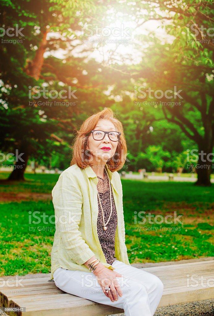 Portrait of senior Japanese woman in park stock photo