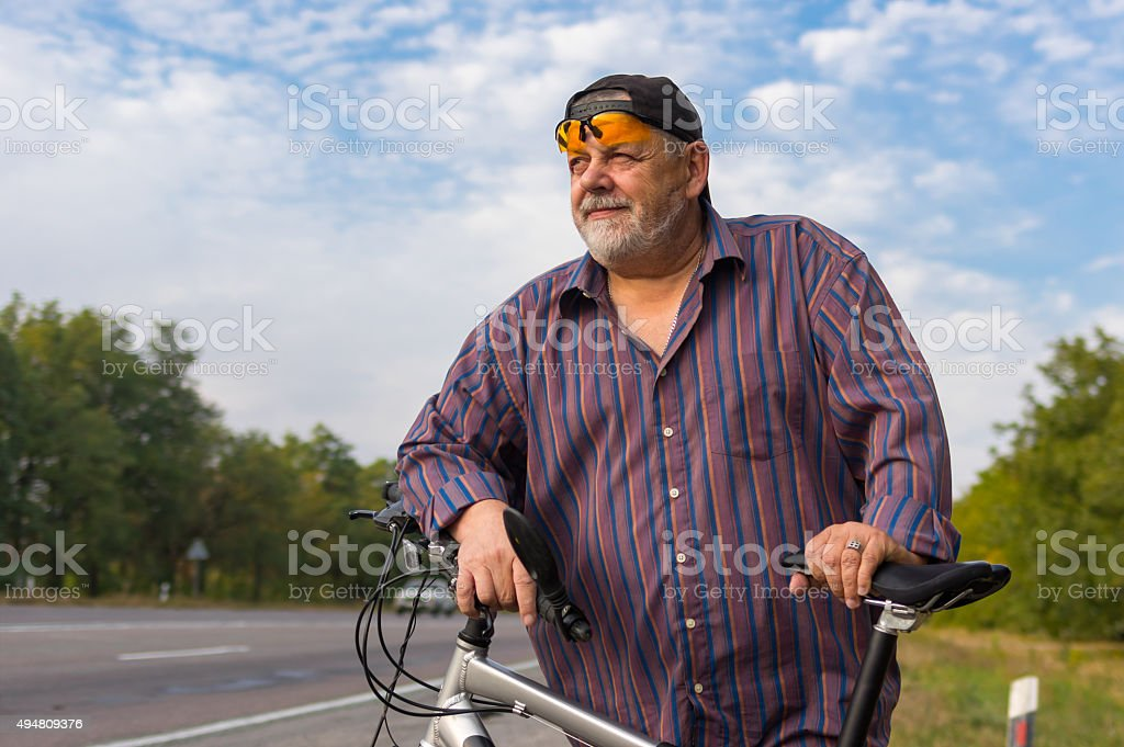 Portrait of senior man getting ready to ride on bicycle stock photo