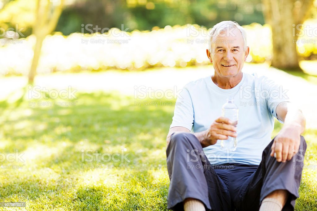 Portrait Of Senior Man Having Water After Workout stock photo