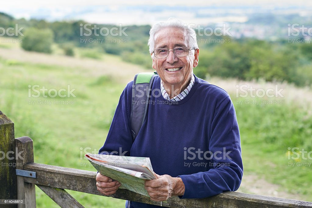 Portrait Of Senior Man Hiking In Countryside stock photo