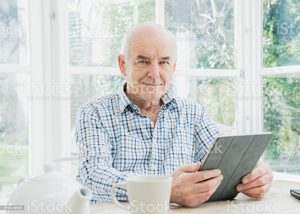 Portrait of senior man holding digital tablet looking at camera stock photo