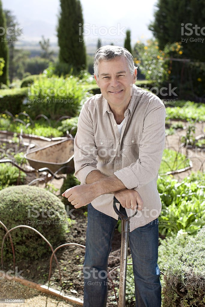 Portrait of senior man leaning on gardening tool in domestic garden royalty-free stock photo