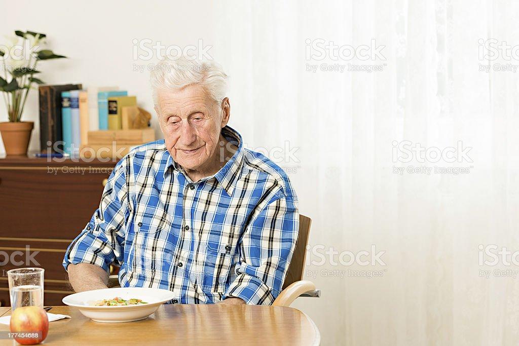 Portrait of senior man sitting at table stock photo