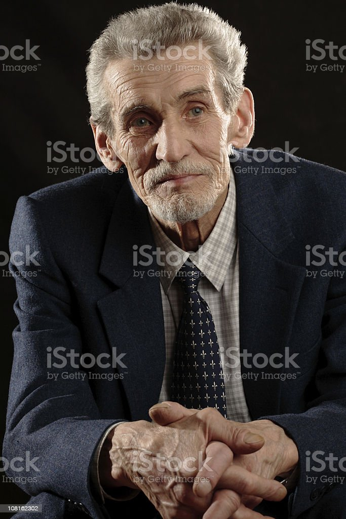 Portrait of Senior Man Sitting Down and Wearing Suit royalty-free stock photo