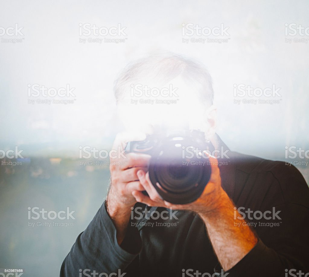 Portrait of  senior man taking photograph with flash stock photo