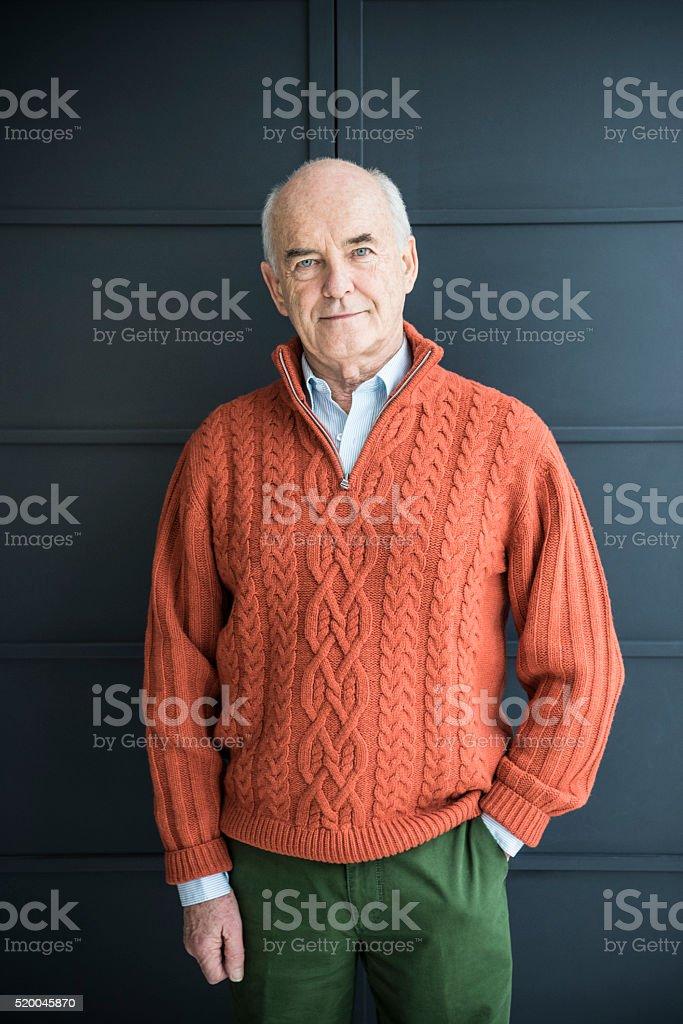 Portrait of senior man wearing orange sweater stock photo