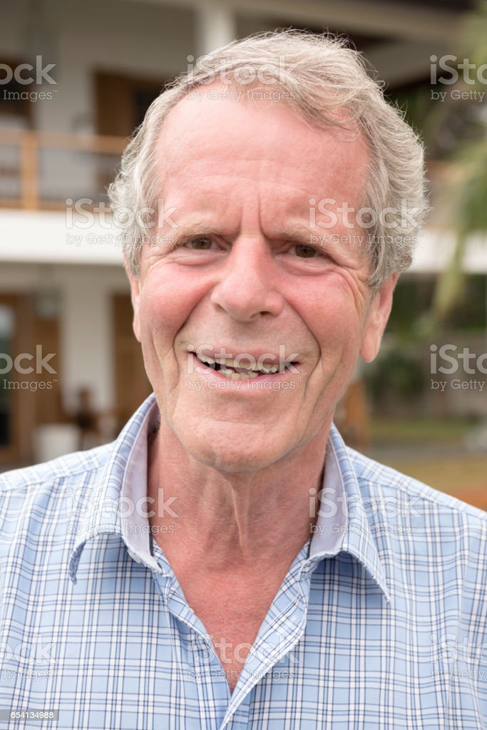 Portrait of senior man with gray hair smiling towards camera stock photo
