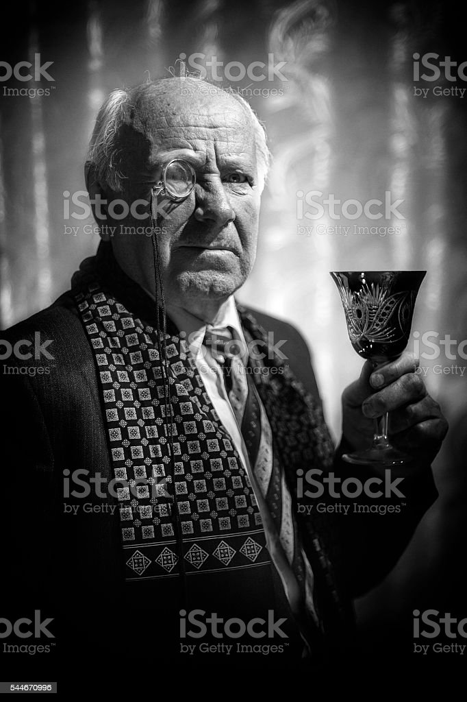 Portrait of Senior Man with monocle and wineglass. stock photo