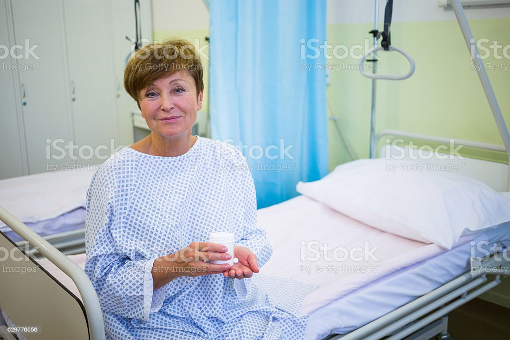 Portrait of senior patient sitting on a bed holding medicine stock photo