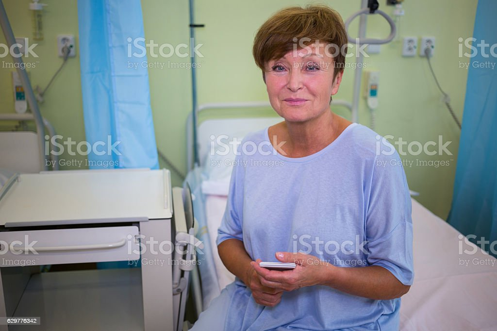 Portrait of senior patient sitting on a bed stock photo