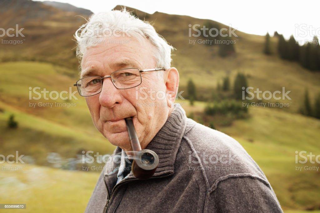 Portrait of Senior Pipe Smoker in the Mountains stock photo