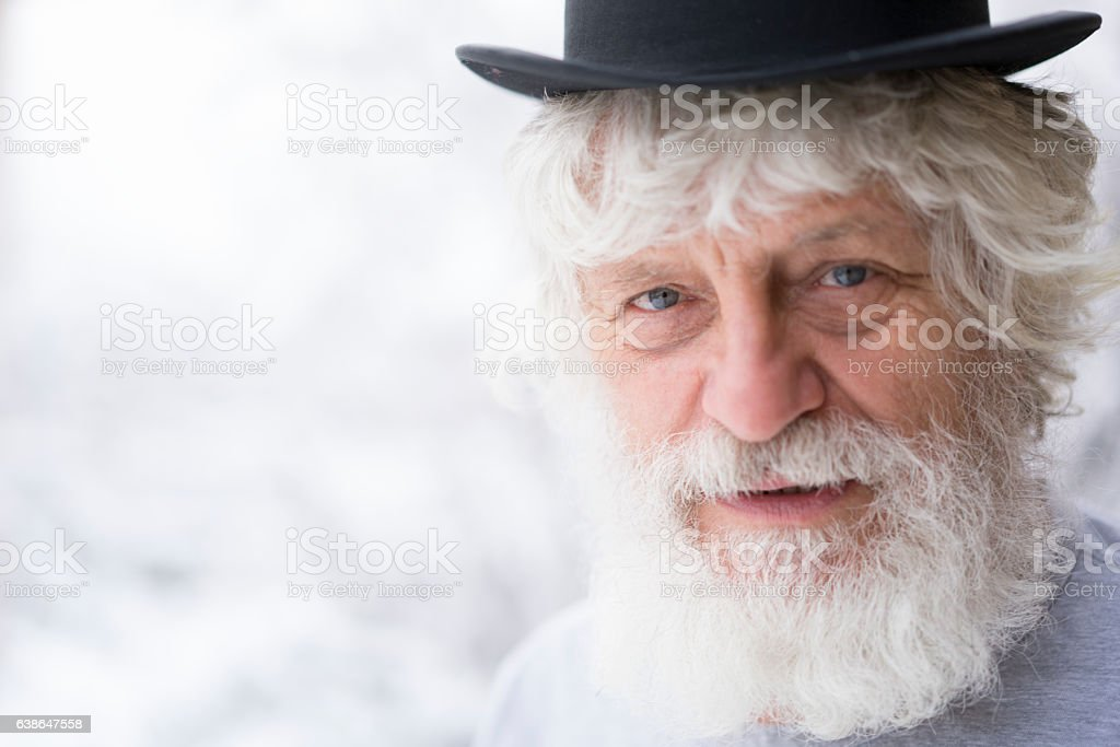 Portrait of senior with cylinder hat and blurred snow background stock photo
