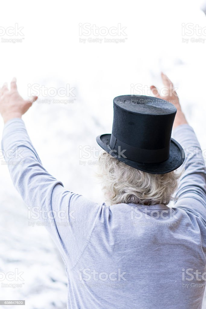 Portrait of senior with cylinder hat and reised hands stock photo