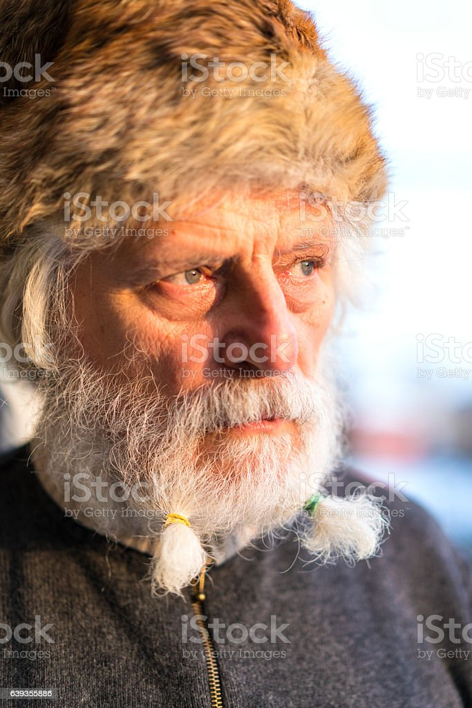 Portrait of senior with white beard and blurred snow  background stock photo