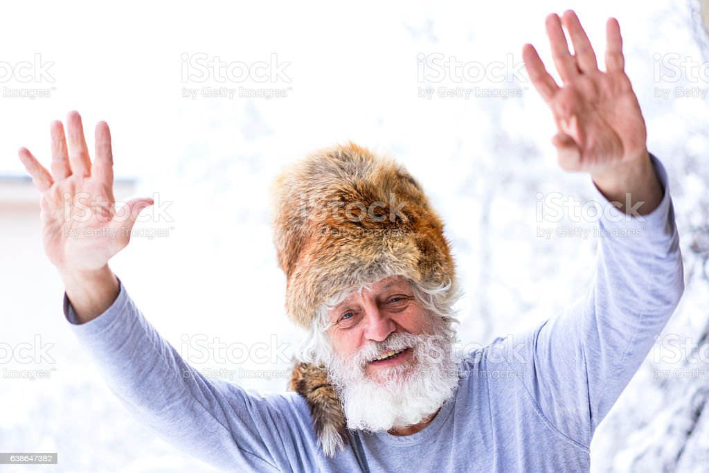 Portrait of senior with white beard and reised hands stock photo