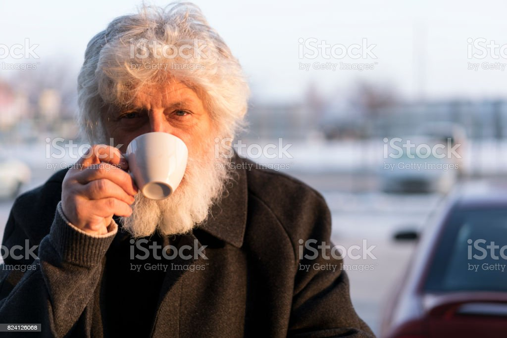 Portrait of senior with white beard drinking coffee stock photo
