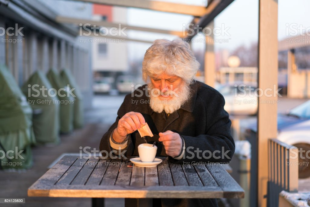 Portrait of senior with white beard puting sugar in his coffee stock photo